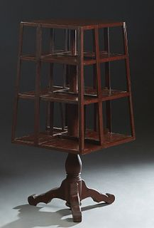 American Carved Mahogany Revolving Bookmill, early 20th c., with slatted sides, on a circular support to tripodal flat splayed legs, H.- 44 in., W.- 1