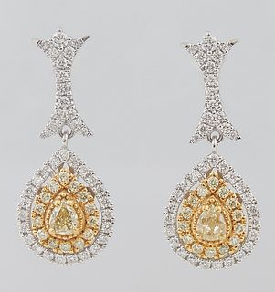 Pair of 18K White Gold Pendant Earrings, the diamond mounted screwback stud, to a long link and a pendant with a pear shaped yellow diamond atop a bor