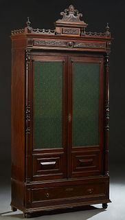 French Provincial Carved Walnut Bookcase, c. 1870, the ornate stepped pierced crown over setback double green glass doors, flanked by turned pilasters