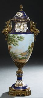 Sevres Style Bronze Ormolu Mounted Covered Porcelain Vase, 20th/21st c., in cobalt blue with gilt decoration, the bronze finialed cover over sloping s