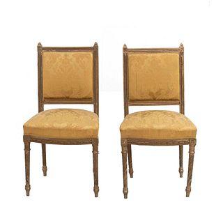 Par de sillas. Siglo XX. Estilo francés. Con respaldos cerrados y asientos en tapicería color amarillo.