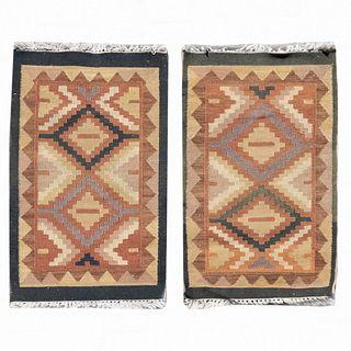 Lote de 2 tapetes para pie de cama. Siglo XX. Estilo Kilim. Elaborados en fibras de lana y algodón. Decorados con motivos geométricos.