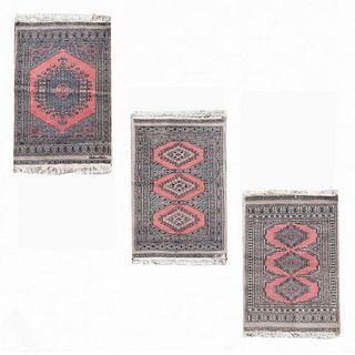 Lote de 3 tapetes, pie de cama. Siglo XX. Estilo bokhara. Elaborados en fibras de lana y algodón. Decorados con motivos geométricos.