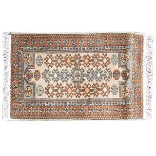 Tapete, pie de cama. Siglo XX. Estilo turcomano. Elaborado a en fibras sintéticas. Decorado con elementos geométricos.