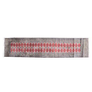 Tapete de pasillo. Siglo XX. Estilo bokhara. Elaborado en fibras sintéticas. Decorado con motivos geométricos en color carmín.