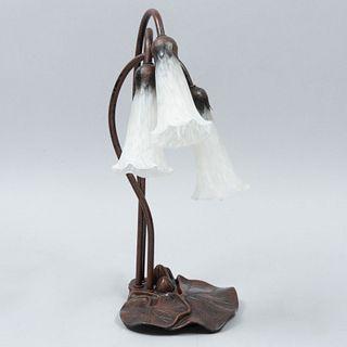 Lámpara de mesa. Siglo XX. Diseño floral. Elaborada en metal. Acabado patinado. Electrificada para 3 luces. Con pantallas de vidrio.