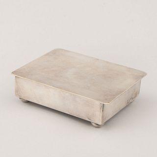 Alhajero. México. Siglo XX. Elaborado en metal plateado con interior de madera. Con cubierta abatible y soportes boleados.