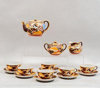 Juego de té. Japón. SXX Estilo Satsuma. Elaborado en porcelana. Consta de: tetera, azucarera, cremera y 6 ternos. Piezas: 15
