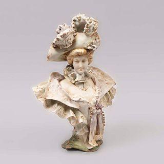 Busto de dama. Austria. Siglo XX. Elaborada en porcelana de Bohemia. Marca Turn Teplitz. Decorada con esmalte dorado. 32.5 cm altura