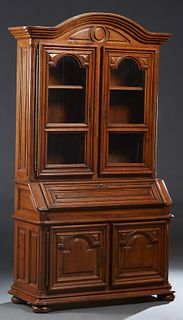 French Louis XIV Style Carved Oak Secretary Bookcase, 19th c., the arched stepped crown over arched glazed doors with iron fiche hinges and brass escu
