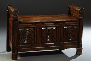 French Empire Style Carved Walnut Hall Bench, 19th c., with rolling pin arms flanking the lifting lid, over a front with three relief carved concentri