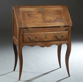 French Louis XV style Carved Walnut Slant Front Secretary, early 20th c., the slant lid opening to an interior fitted with drawers and shelves, over a