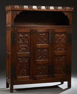 French Provincial Renaissance Style Carved Oak Sideboard, 19th c., the scrolled crown over open storage above three highly carved fielded panel doors