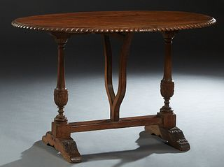 French Renaissance Style Carved Pine Oval Table, 19th c., the gadrooned edge oval top on a trestle form base joined by a rectangular stretcher, having