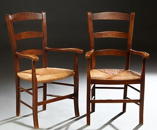 Pair of French Provincial Carved Beech Rush Seat Armchairs, early 20th c., the arched canted curved ladderback over flat curved arms, above a bowed ru