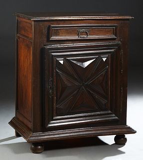 French Provincial Louis XIII Style Carved Oak Confiturier, 19th c., the stepped rounded edge top over a frieze drawer and a lower cupboard door with i