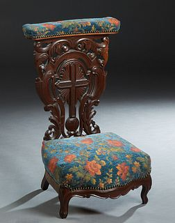 French Carved Oak Prie Dieu, 19th c., the curved upholstered arm rest over an elaborately carved cross and scroll back, to a bow front kneeler, on cab