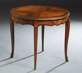 French Ormolu Mounted Inlaid Mahogany and Rosewood Coffee Table, 20th c., the circular top within a brass band, over a shaped scalloped skirt, on cabr
