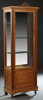 French Louis XVI Style Carved Oak Vitrine, early 20th c., with a pierced ribbon crest, over a center door with a beveled glass upper panel over a fiel