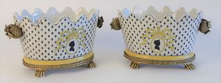 Pair of Porcelain Cachepots, with painted and enamel decoration, on brass stands with paw feet, length 11 inches, height 6 inches.