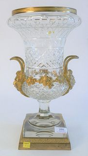 French Crystal and Gilt Bronze Urn, having handles with face masks; on square, gilt, bronze base, height 16 inches.