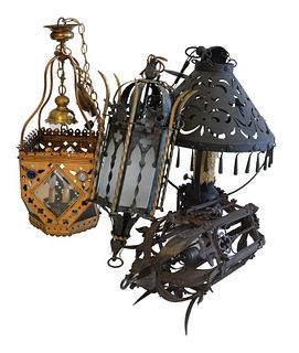 Four Gothic Revival Hanging Lanterns, to include one wrought iron, one painted tole with glass shades, one brass with beveled glass panels and jeweled