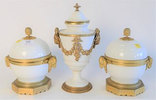 Three French Porcelain Covered Urns, with gilt bronze mounts and rams head handles, set on gilt bronze bases, height 8 inches.