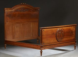 French Louis XVI Style Carved Walnut Double Bed, early 20th c., the arched floral carved headboard joined by wooden rails and a fielded panel footboar