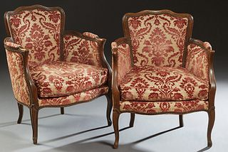 Pair of Louis XV Style Carved Beech Bergeres, 20th c., the arched curved back over upholstered arms and a bowed loose cushion seat, on scrolled cabrio