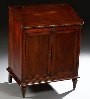 French Louis Philippe Carved Mahogany Slant Top Desk, 19th c., the lift top lid over open storage and double cupboard doors, on a plinth base on turne