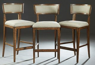 Set of Three Contemporary Carved Mahogany Bar Stools, 20th c., the curved cushioned canted back to a trapezoidal cushioned seat, on tapered square leg