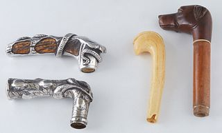 Group of Four Cane or Umbrella Handles, early 20th c., one of antler mounted with a coiled sterling snake; one sterling with relief floral decoration;