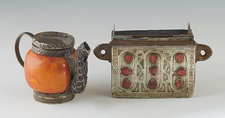 Two Moroccan Pieces, 20th c., consisting of a stamped metal Qur'an holder pendant, with incised decoration, one side mounted with 9 red stones, design