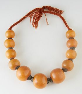 Moroccan Berber Amber Resin Necklace, 20th c., with eleven large graduated beads, with metal spacers, on a twisted wool cord, L.- 18 in.