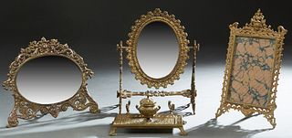 Four Desk Pieces, early 20th c., consisting of a bronze inkwell pen tray; a gilt iron easel picture frame; an iron easel beveled mirror with putti sur