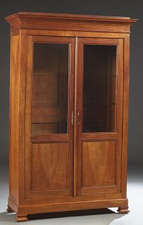 French Louis Philippe Carved Cherry Bookcase, 19th c., the stepped edge top over double doors with glazed upper panels over wood lower panels, on a pl