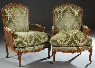 Pair of French Louis XV Style Carved Beech Fauteuils, 20th c., the arched floral carved crest rail to an upholstered back, over upholstered double can