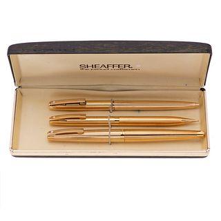 Pluma fuente, bolígrafo y lapicero Sheaffer. Cuerpo en acero dorado. Punto en oro amarillo de 14k. Estuche original.