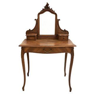 Tocador con espejo.  Siglo XX.  Estilo Luis XV.  En talla de madera de nogal.  Con espejo irregular biselado.