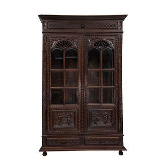 Librero.  Francia.  Siglo XX.  Estilo Bretón.  En talla de madera de roble. Con 2 cajones inferiores, 2 puertas con cristales.