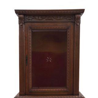 Gabinete. Francia. Siglo XX. En talla de madera de roble. Con puerta abatible de vidrio y cajón inferior.