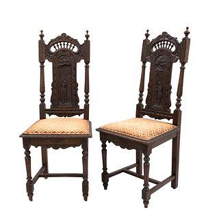 Par de sillas. Francia. Siglo XX. Estilo Bretón. En talla de madera de roble. Con respaldos semiabiertos.