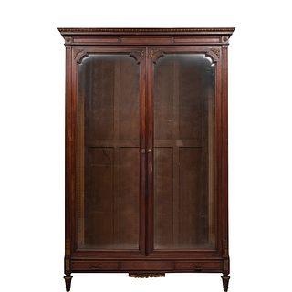 Librero.  Francia.  Siglo XX.  En talla de madera nogal.  Con cajón con tiradores de metal dorado, 2 puertas abatibles.
