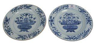 Set of Eight Blue and White Plates having painted central floral basket, 19th century, diameter 9 inches.