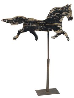 Primitive Wood Horse Weathervane crudely carved in trotting position and painted black, mounted on an iron stand, length 40 inches.
