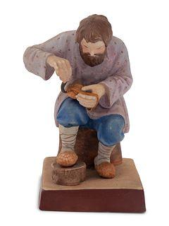 A Russian Porcelain Figure of a Bast Shoe Maker