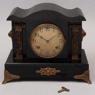 Reloj de chimenea. Estados Unidos. Siglo XX. Estilo Napoleón III. Elaborado en madera color negro con aplicación de metal dorado.