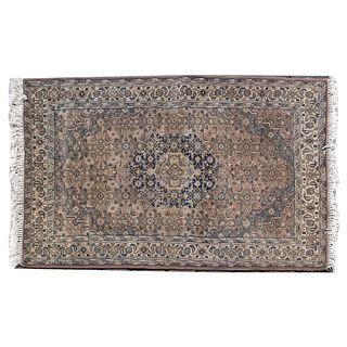 Tapete. Siglo XX. Estilo turcomano. Anudado a mano en fibras de lana y algodón. Decorado con medallón central.