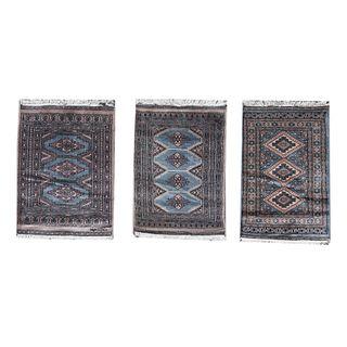 Lote de 3 tapetes, pie de cama. Pakistan, Siglo XX. Estilo Boukhara. Elaborados en fibras de lana. Decorados con motivos geométricos.