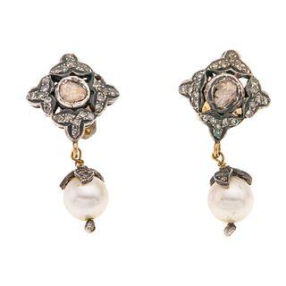 Par de aretes con perlas y diamantes en oro amarillo de 10k y plata. 2 perlas cultivadas color gris de 7 mm. 2 diamantes facetad...